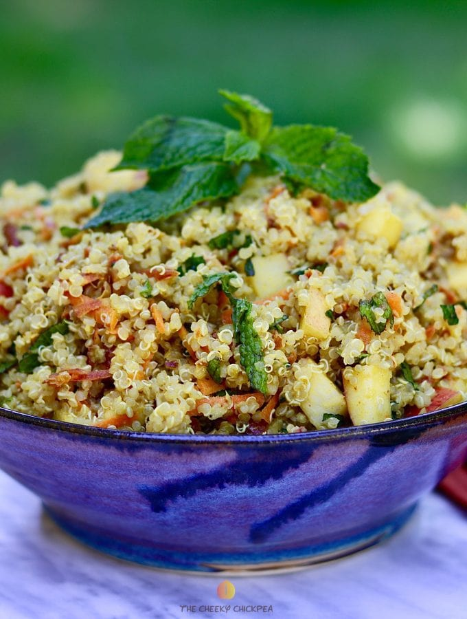 Curried quinoa salad in blue bowl on marble countertop