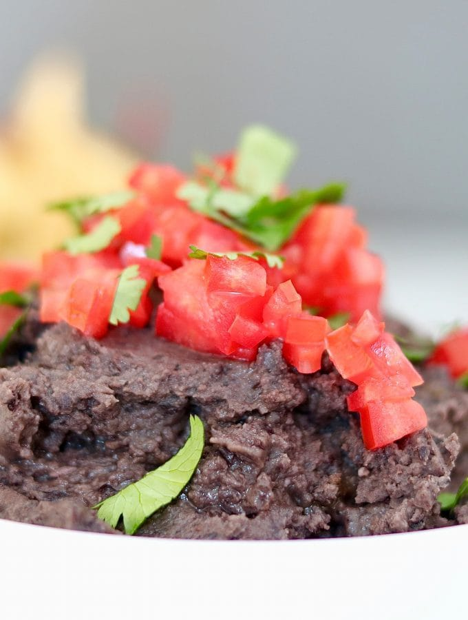 best refried black beans in white bowl on marble countertop with tortilla chips.