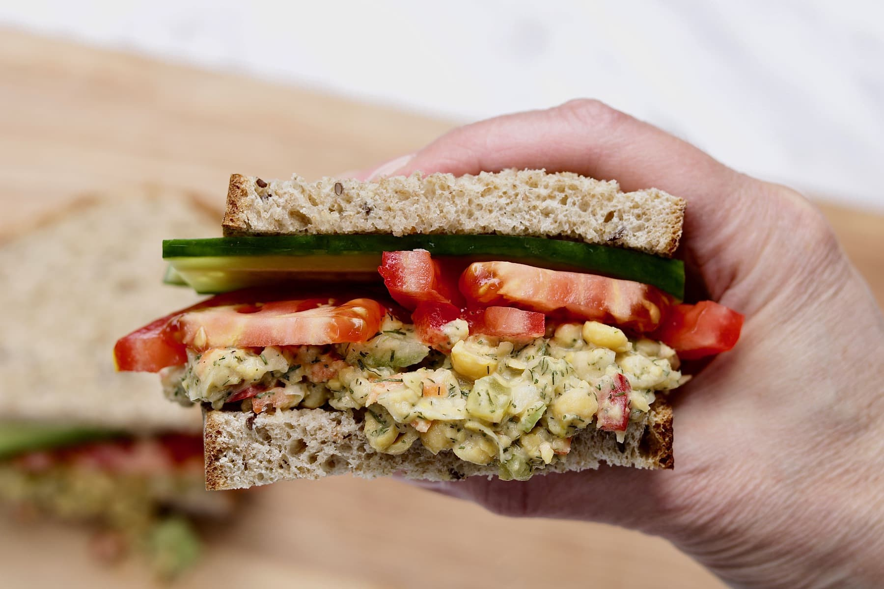 tasty vegan tuna sandwiches held in the air