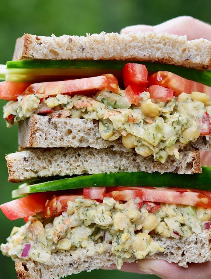 chickpea tuna salad sandwich being held in the air