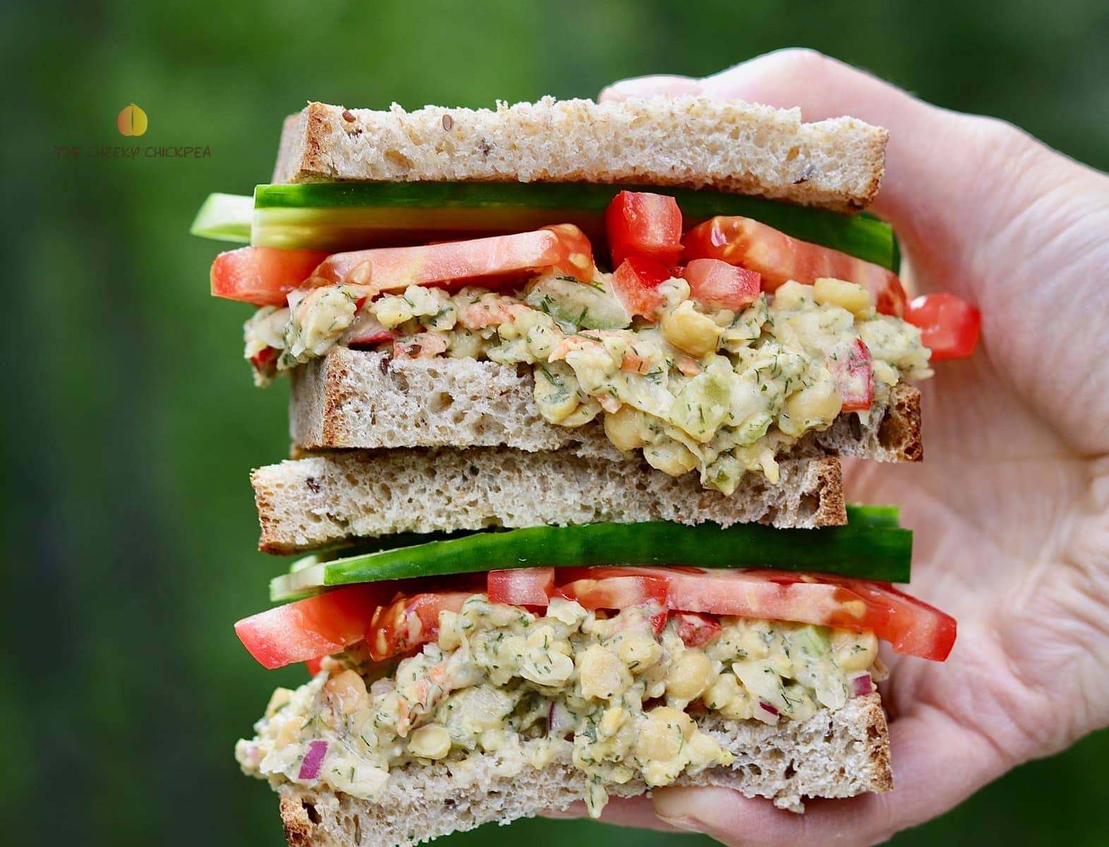 chickpea salad sandwich being held in the air