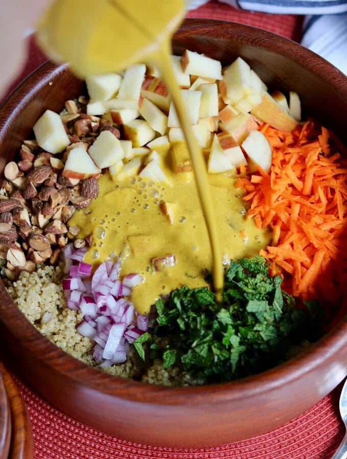 curry dressing being poured on quinoa salad