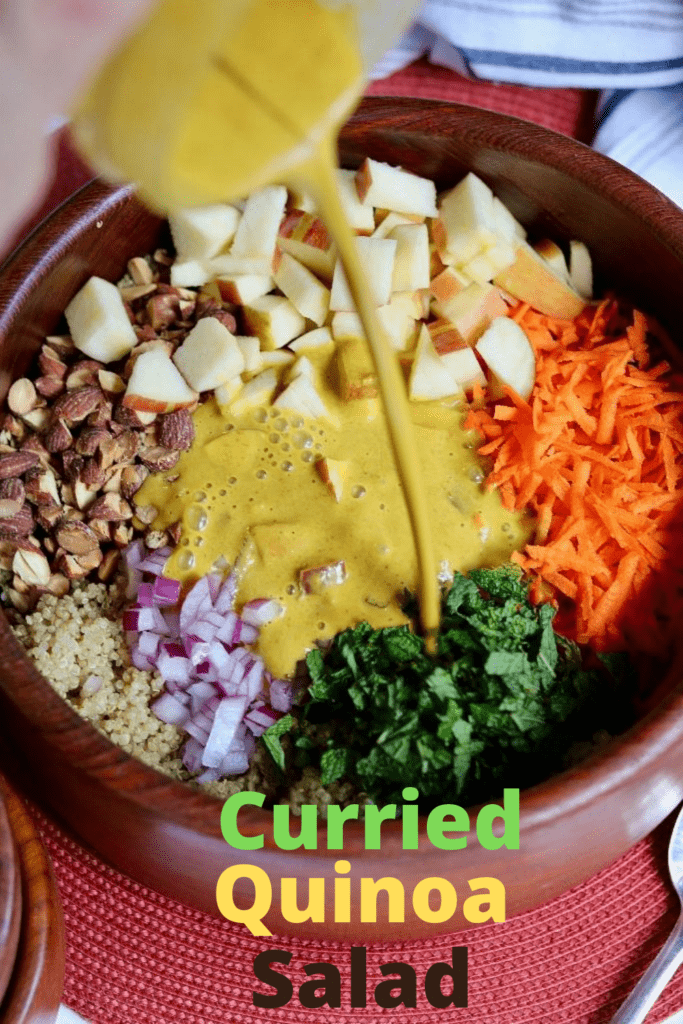 curry dressing being poured over quinoa salad