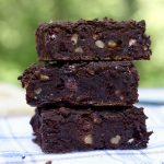 vegan black bean brownies stacked on a blue and white dishcloth