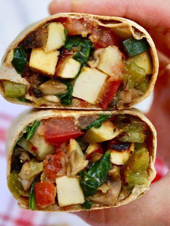 vegan breakfast burrito being held in the air