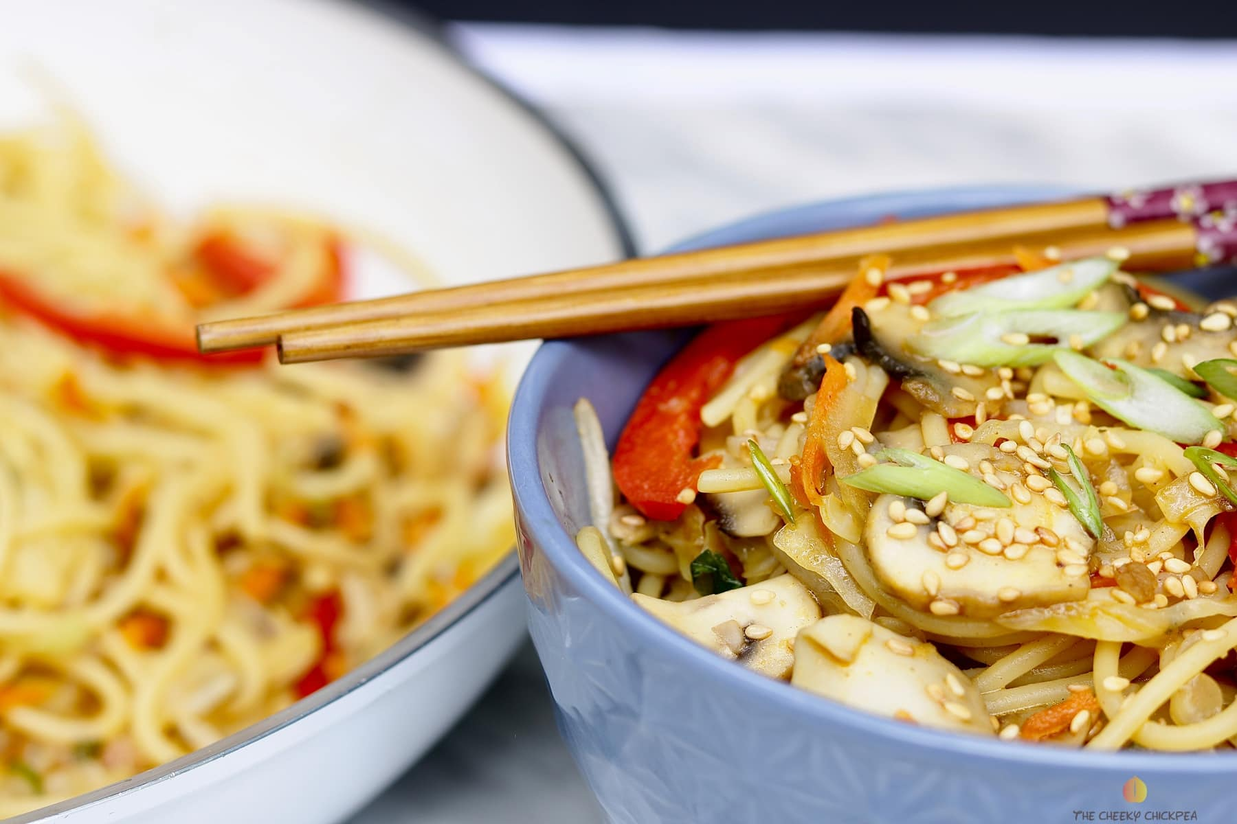 veggie chow mein in a blue bowl with chopsticks