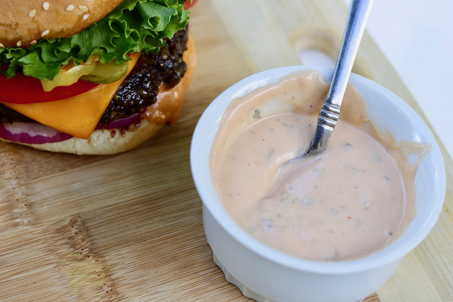 best vegan burger sauce recipe in white bowl on wooden cutting board