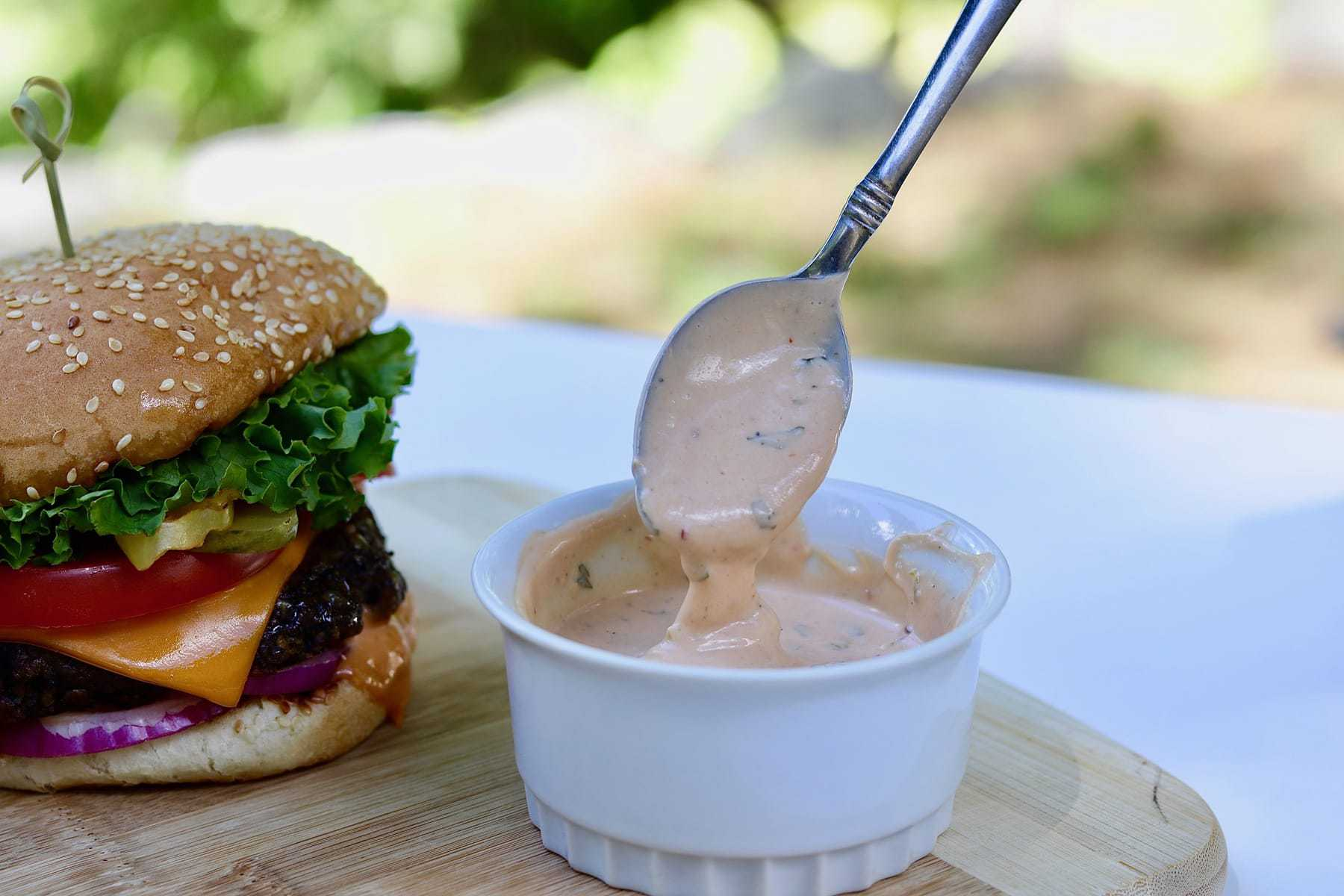 best vegan burger sauce recipe in white bowl on wooden cutting board