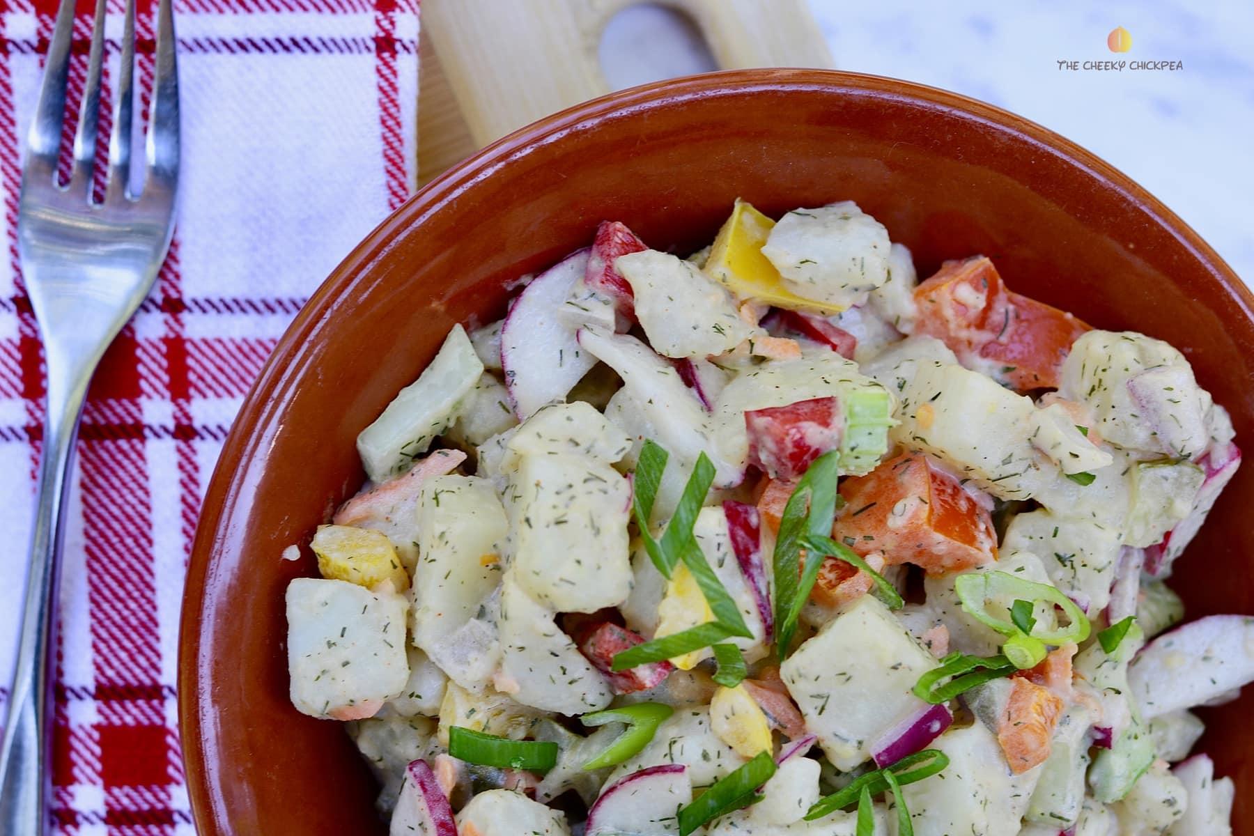 wickedly good vegan potato salad recipe in a brown bowl on a cutting board
