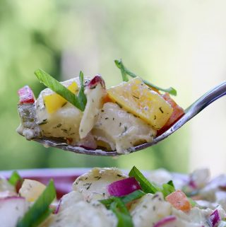 wickedly good vegan potato salad recipe in a brown bowl with a fork