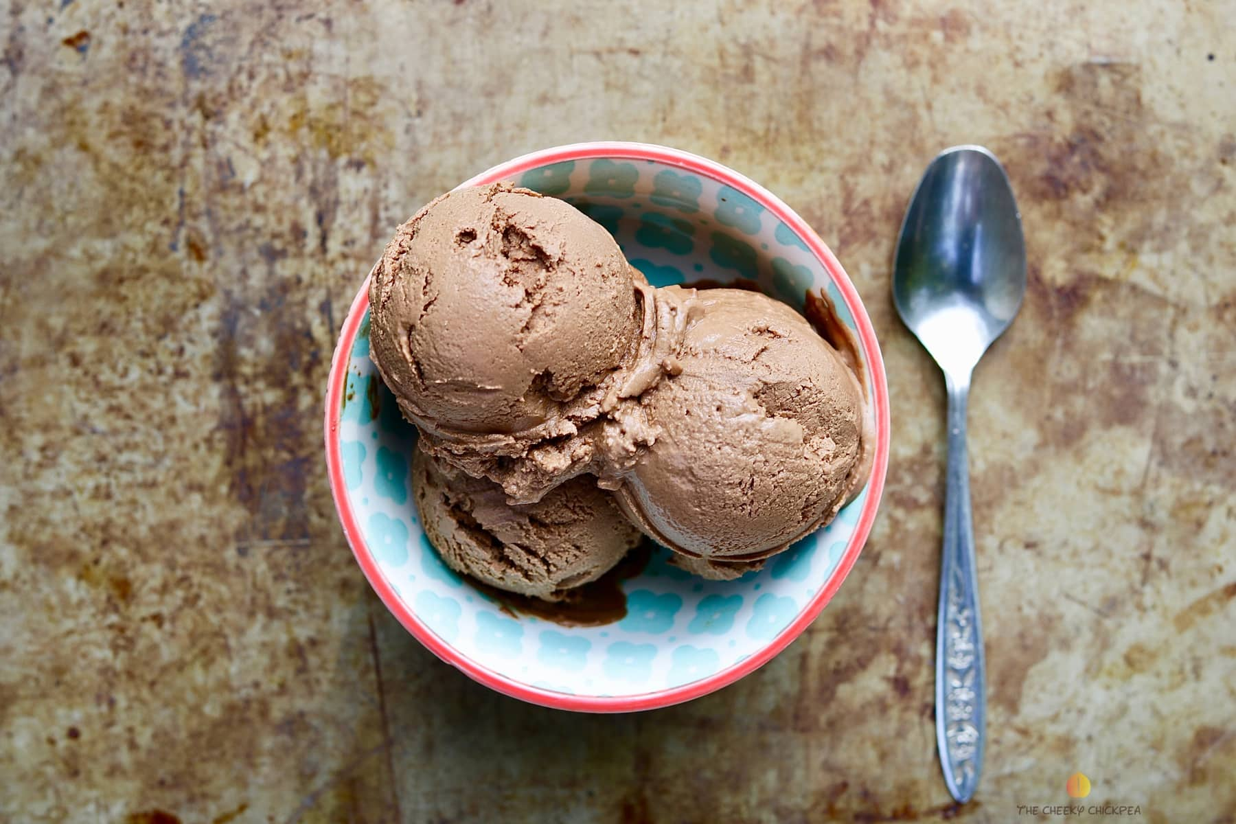 Amazing chocolate malted vegan ice cream in a blue bowl on a baking sheet