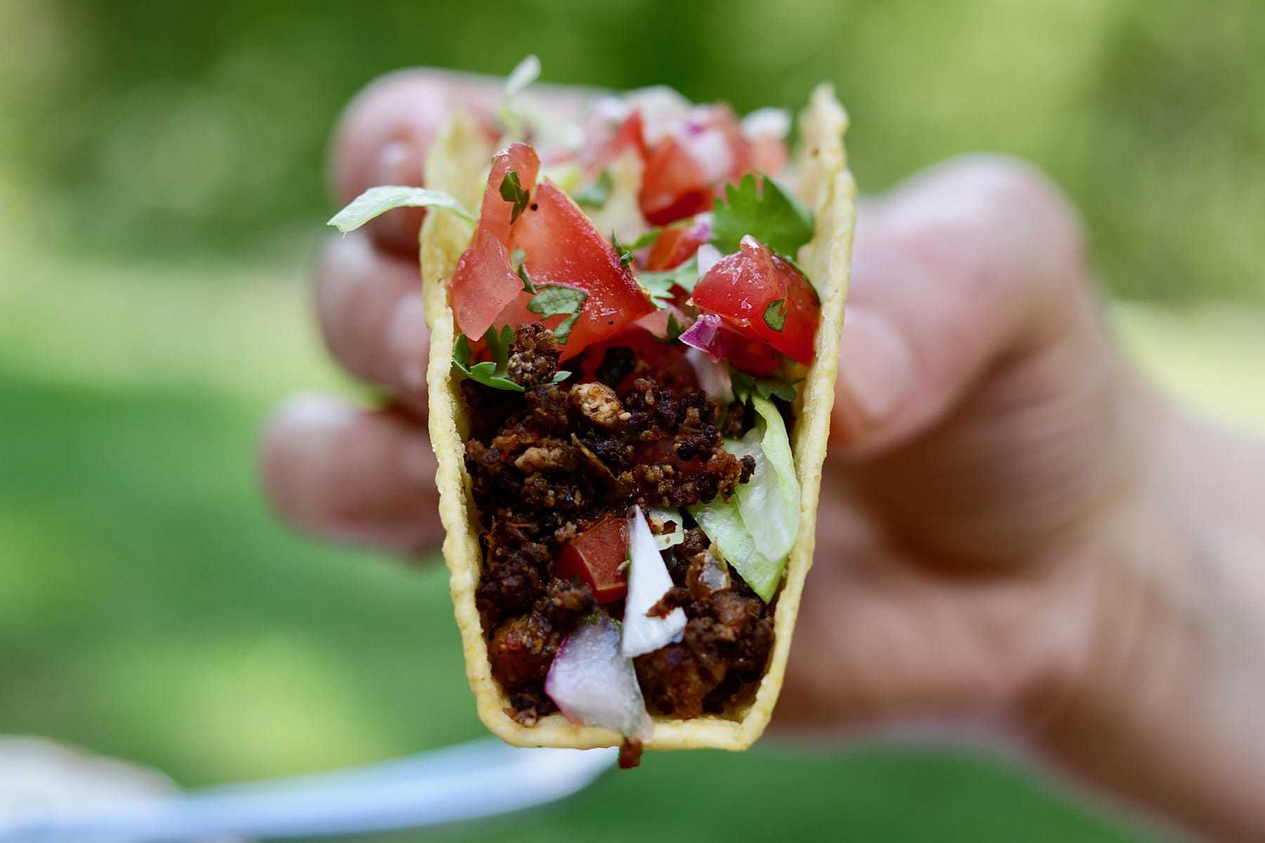 tasty tex mex vegan taco meat recipe in taco shell held in the air