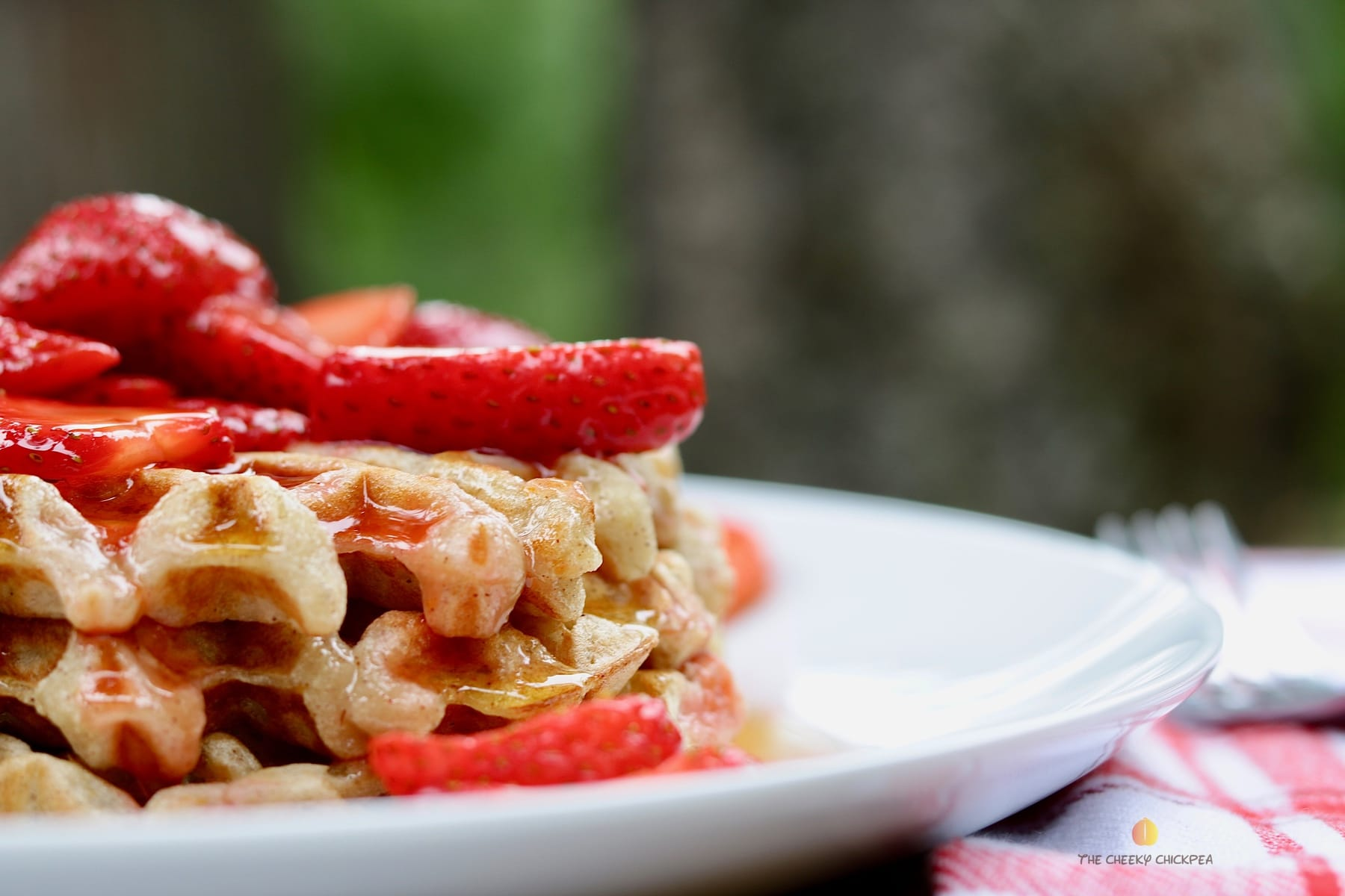 delicious everyday vegan waffles recipe on a white plate with strawberries