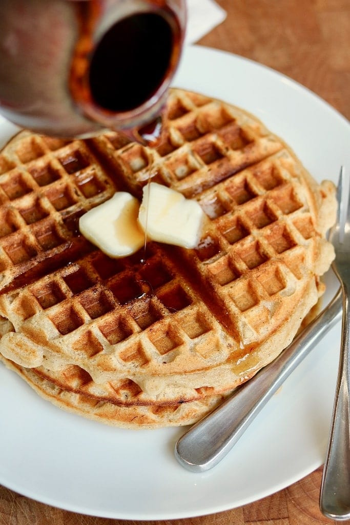 syrup being poured on vegan waffles