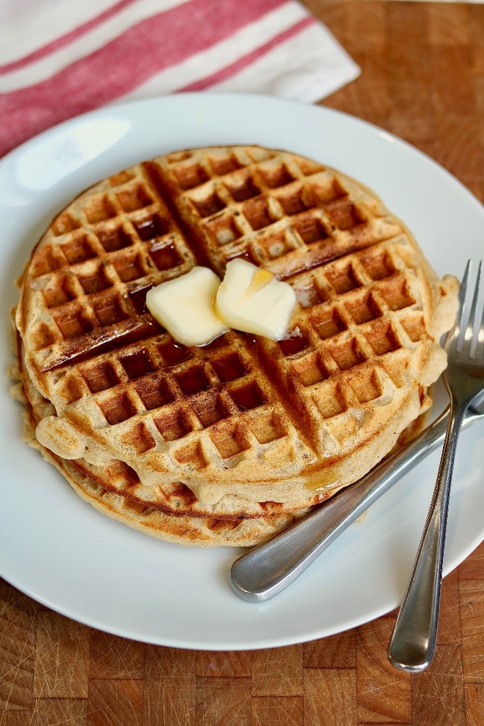 stack of three vegan waffles on a white plate