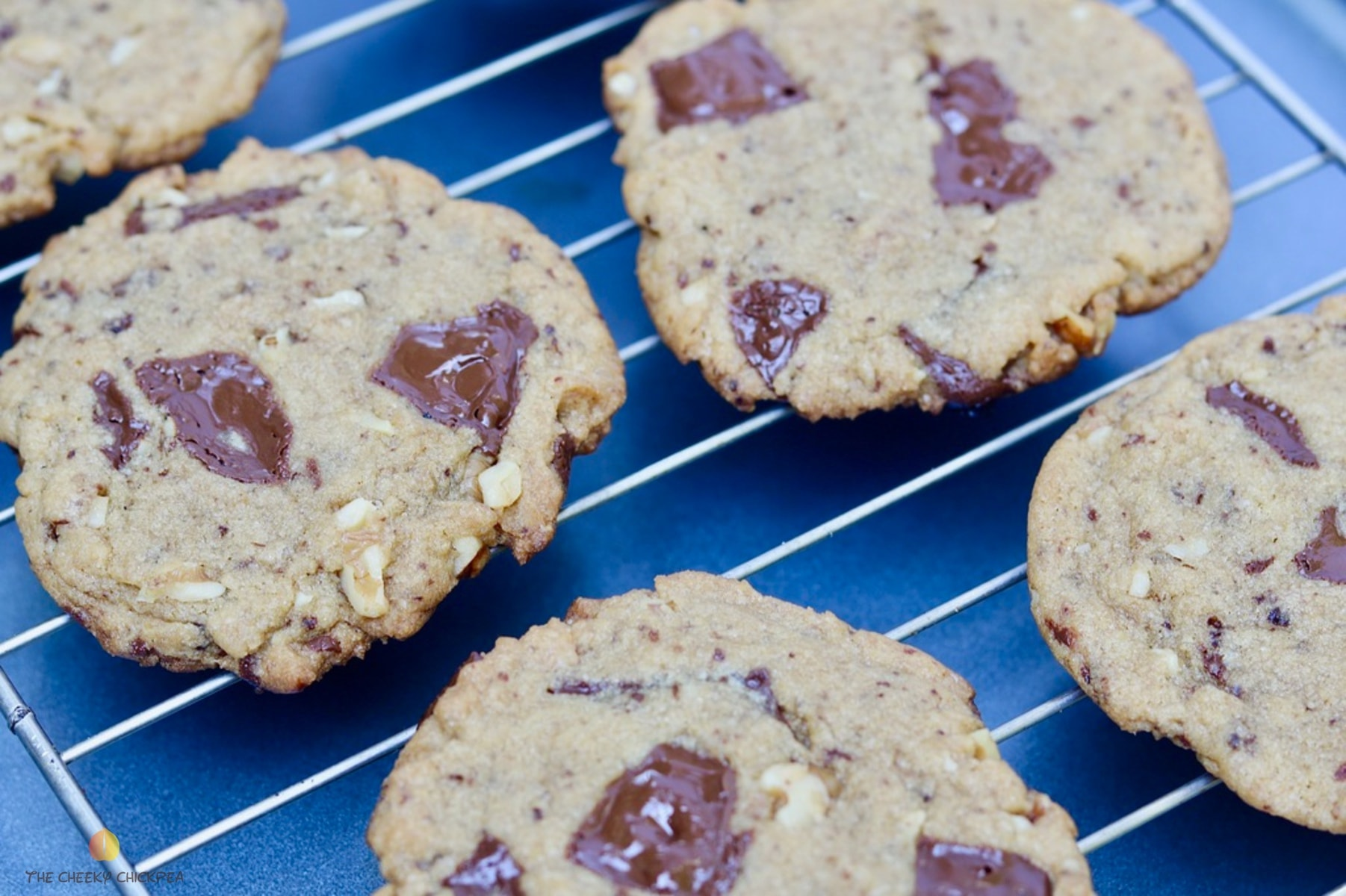 four vegan chocolate chip cookies on a cooling rack