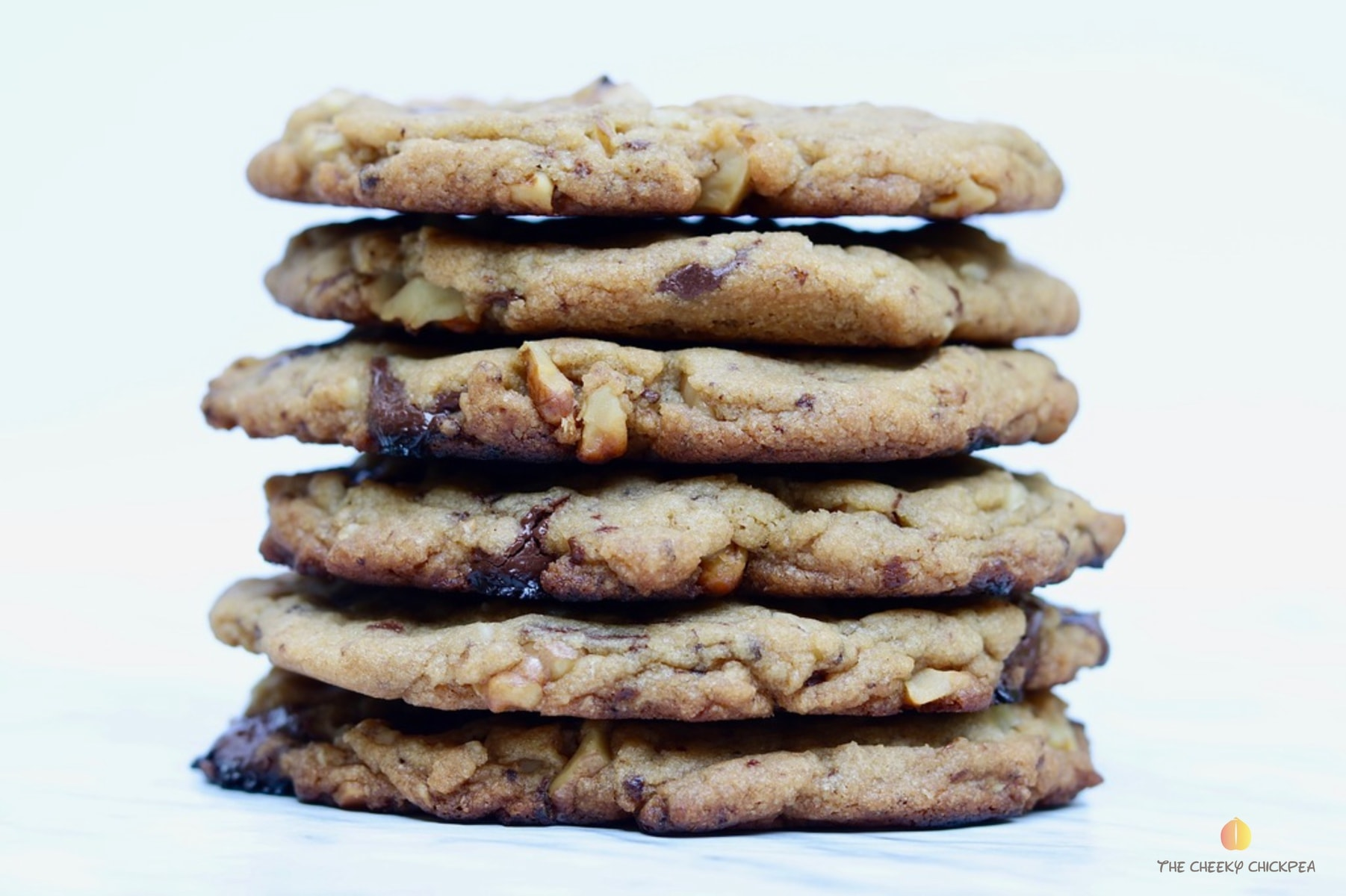 vegan chocolate chip cookies stacked on a marble countertop