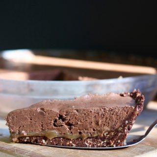 salted caramel vegan chocolate tart on a wooden cutting board