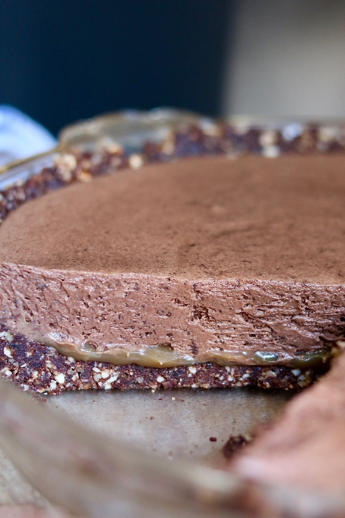 salted caramel vegan chocolate tart in a pie plate with a piece cut out