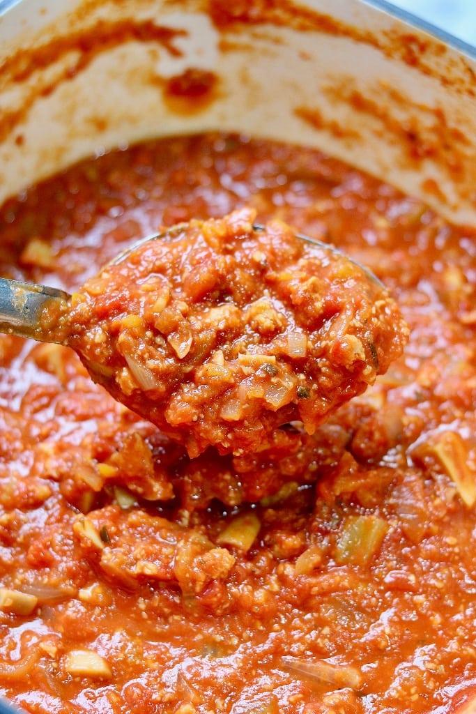 vegan bolognese sauce on a spoon over a pot
