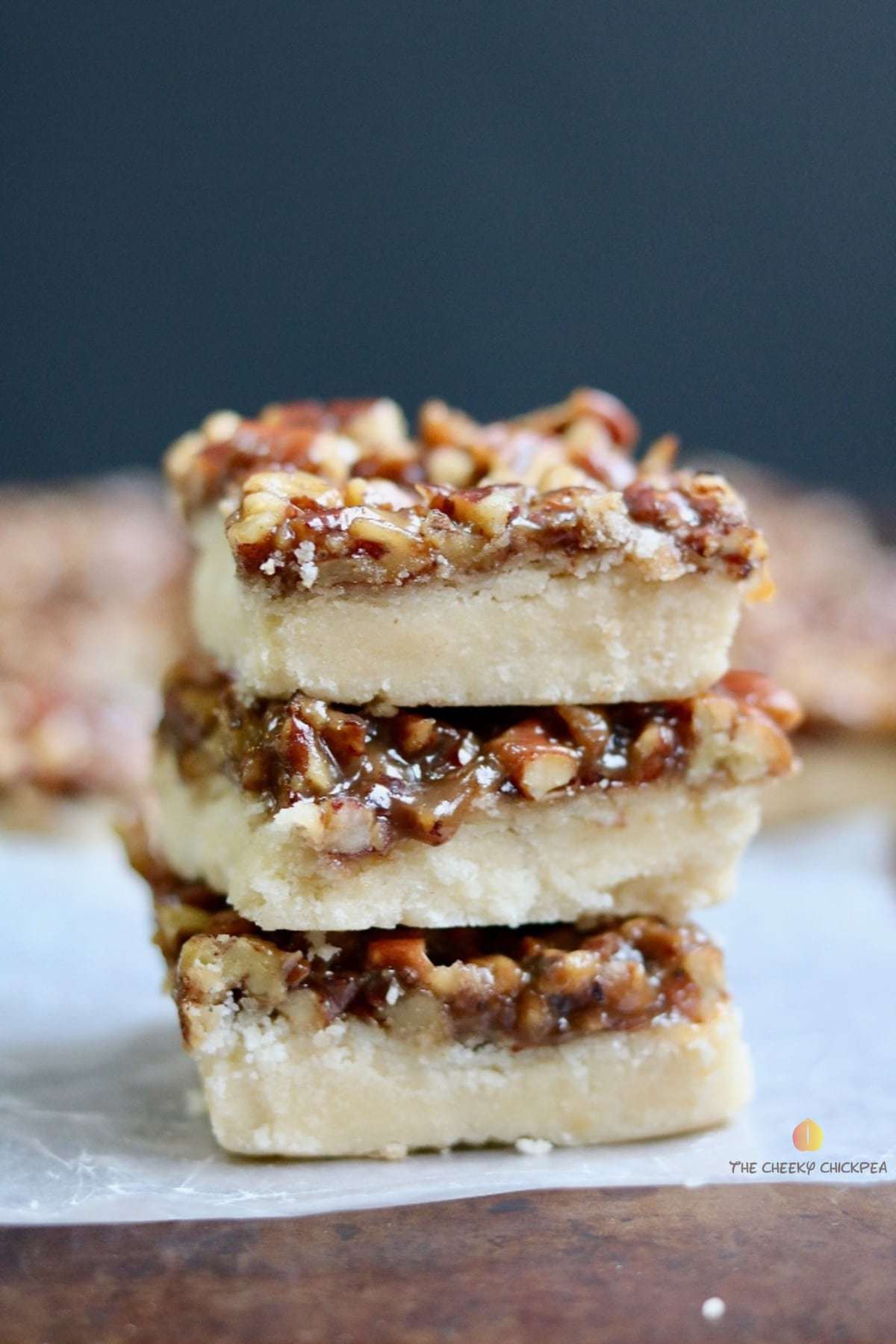 salted caramel & pecan vegan shortbread bars stacked on a counter