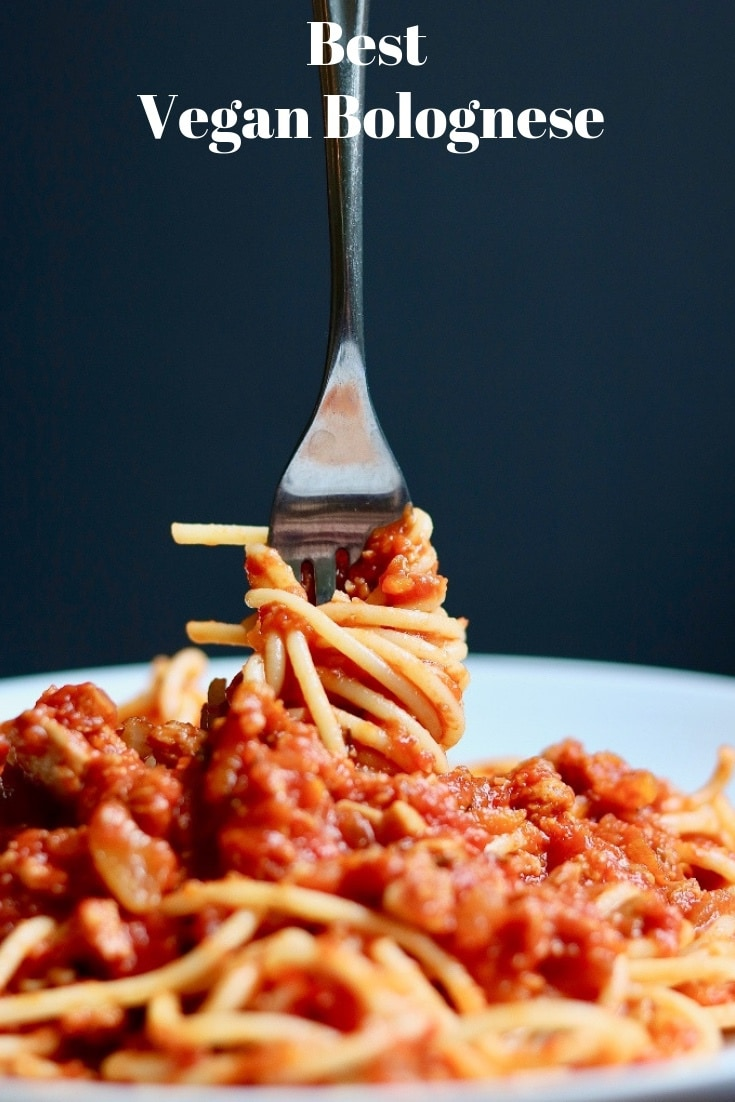hearty vegan bolognese twisted on a fork on a white plate