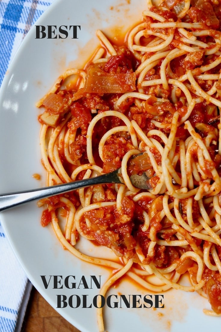 hearty vegan bolognese on a white plate with a fork