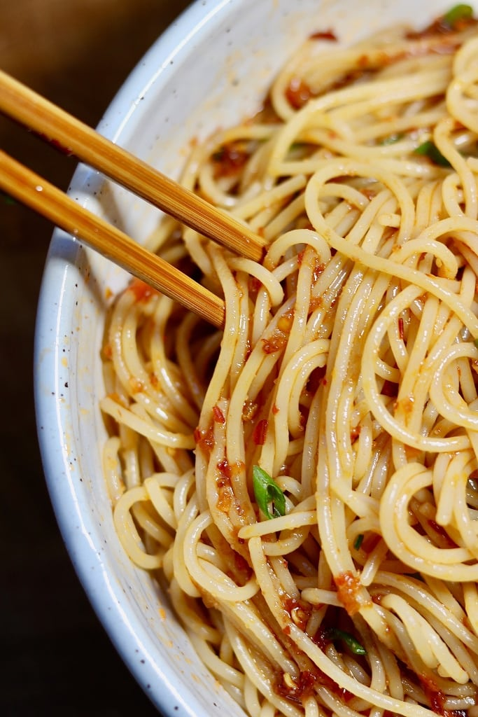 spicy sweet and sour garlic noodles in a white bowl with chopsticks