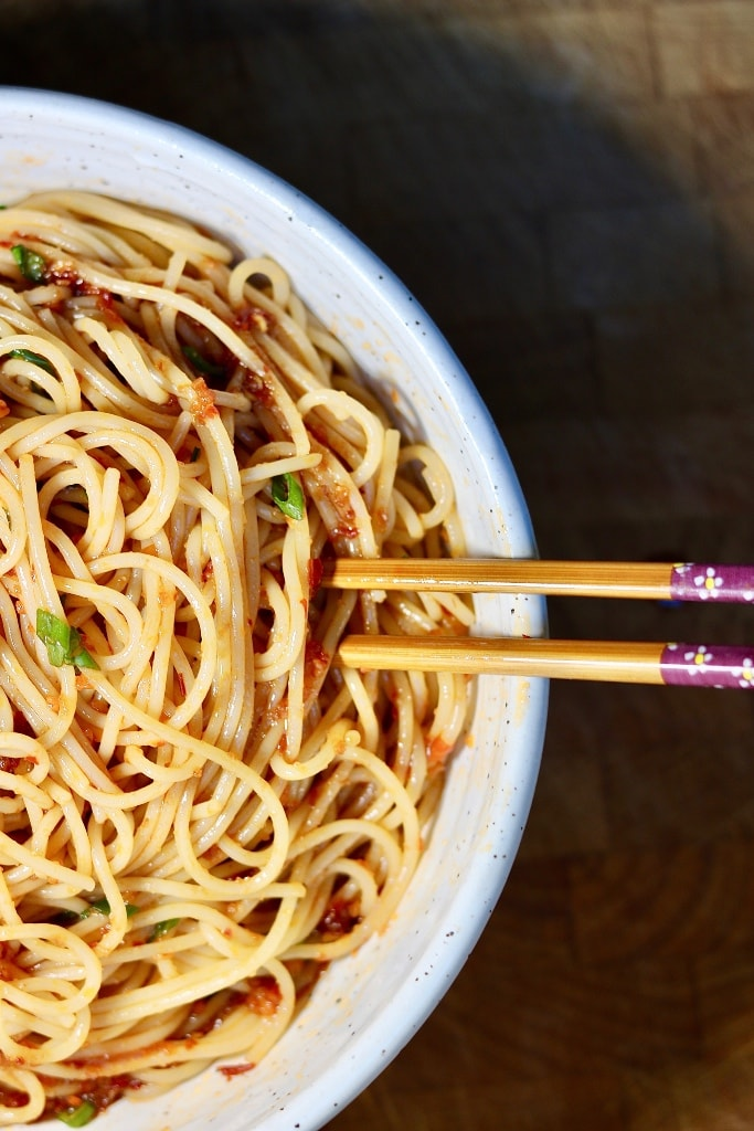 spicy sweet and sour garlic noodles in a bowl with chopsticks