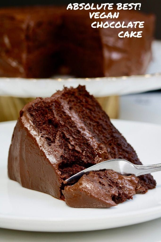 piece of vegan chocolate cake on a white plate with a fork