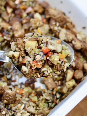vegan stuffing on a serving spoon over a casserole dish