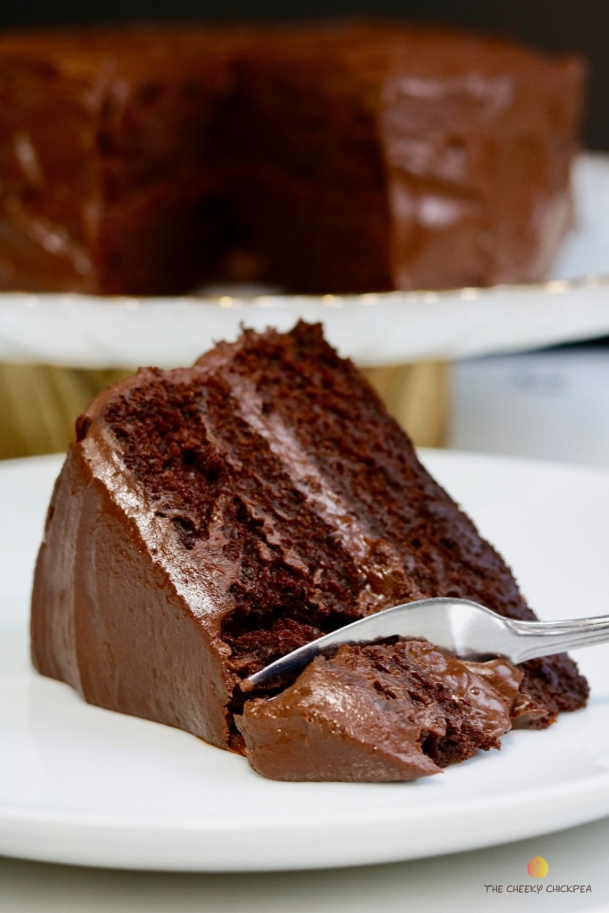 vegan chocolate cake on a white plate being cut with a fork