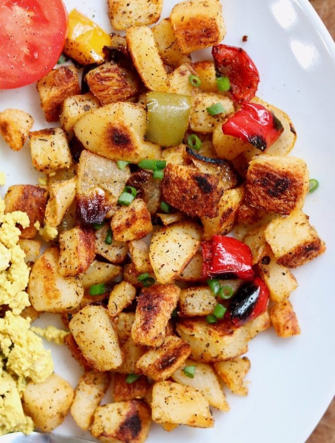 best home fries recipe on a white plate with peppers and onions mixed in