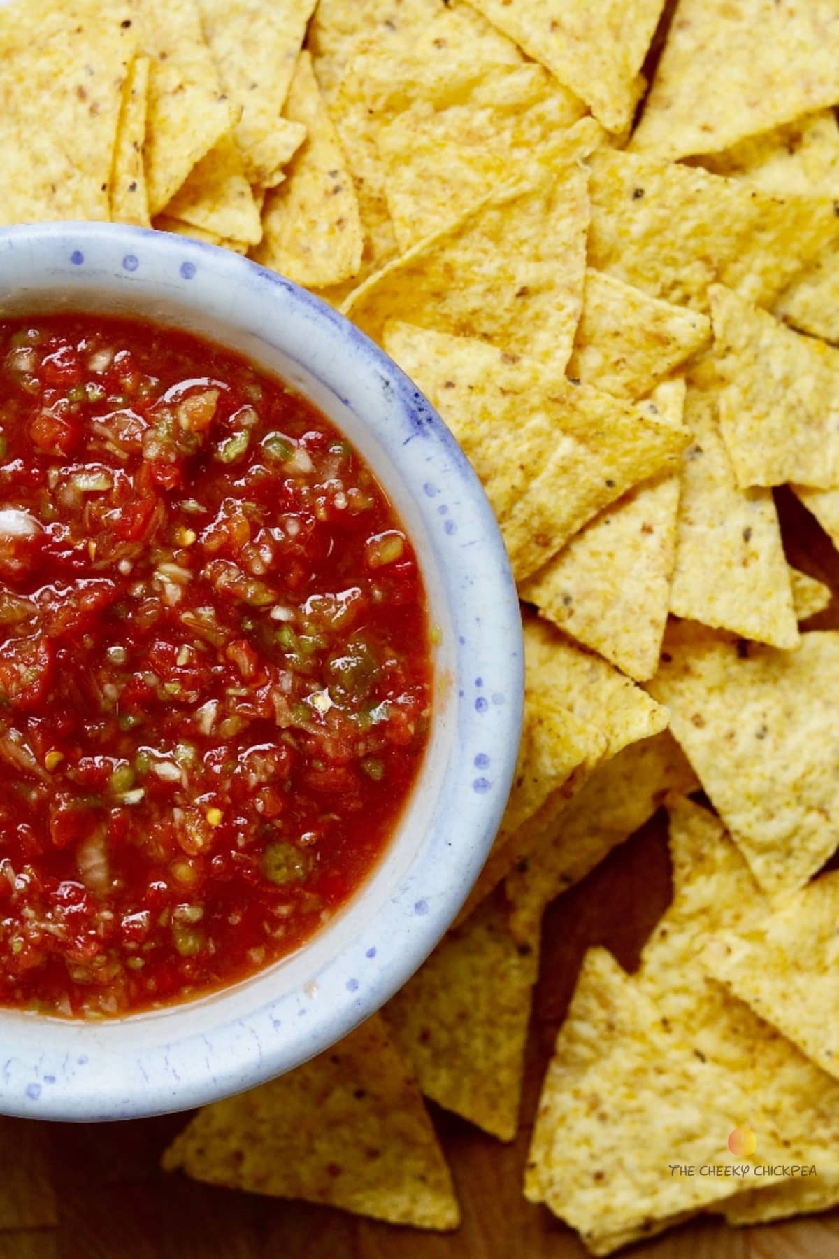 best salsa recipe in blue flecked white bowl surrounded by tortilla chips