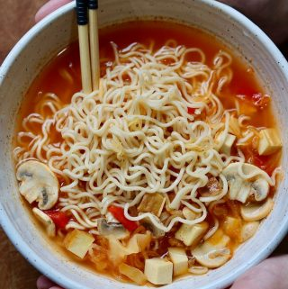 ramen noodle soup in a bowl being held with two hands