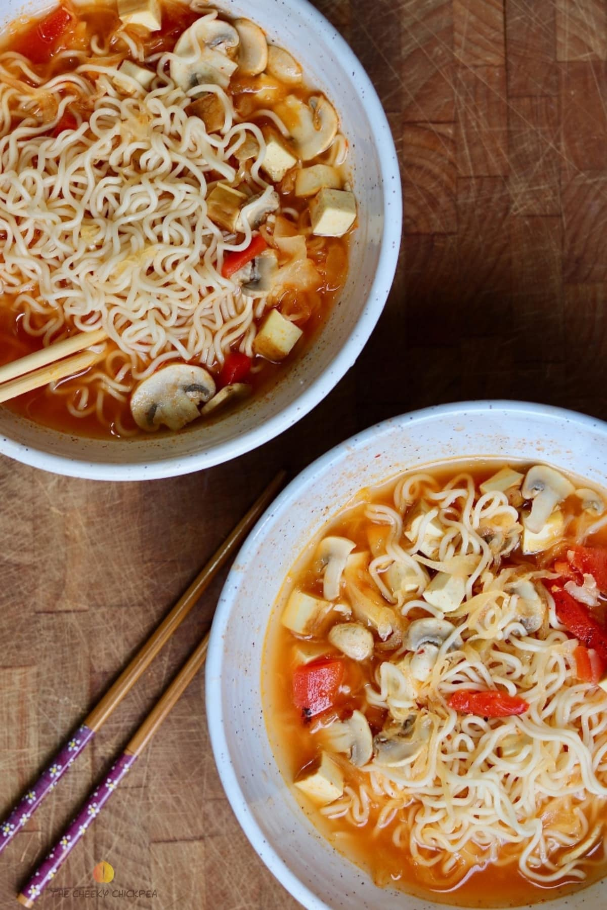 Ramen noodle soup in two white bowls on wooden cutting board