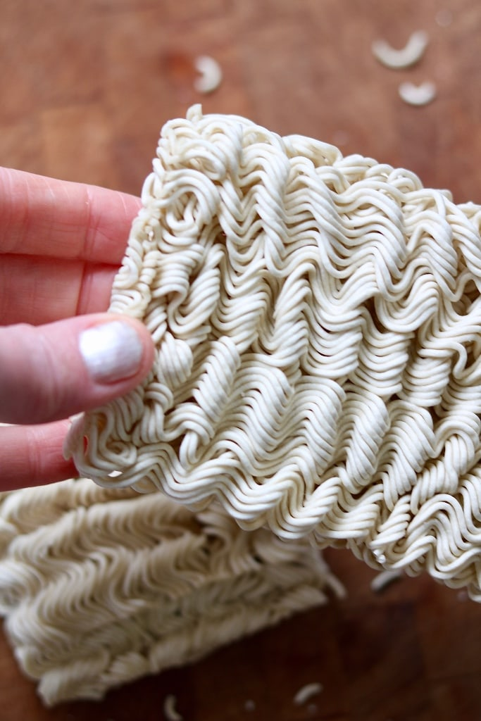 instant ramen noodles for soup being held in hand