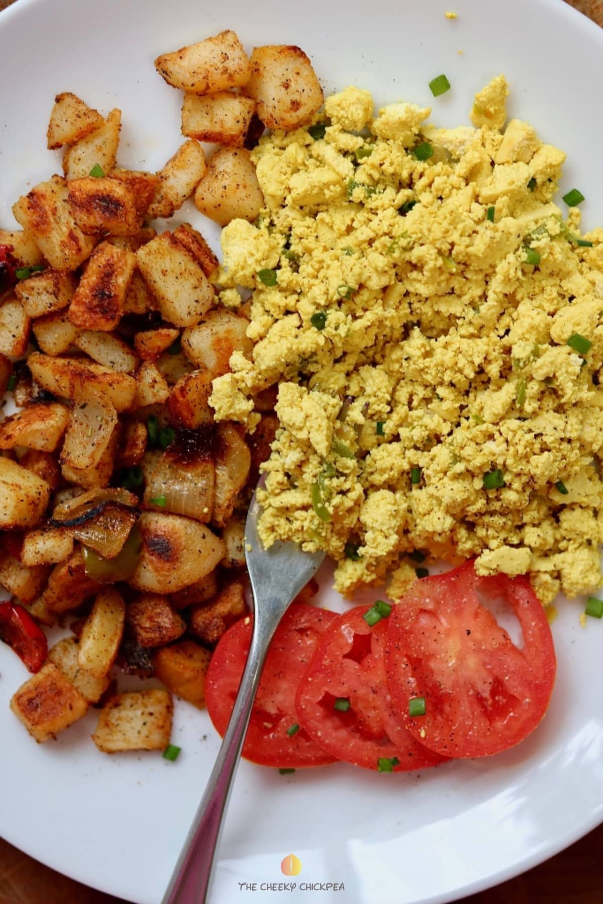 vegan scrambled eggs with a fork on a white plate with tomatoes and potatoes