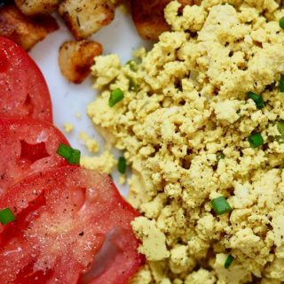 tofu scrambled eggs on a white plate with potatoes and tomatoes