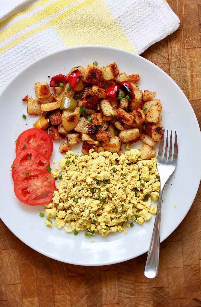 tofu scramble on a white plate with tomatoes and potatoes