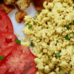 vegan scrambled eggs on a white plate with a fork and tomatoes and potatoes