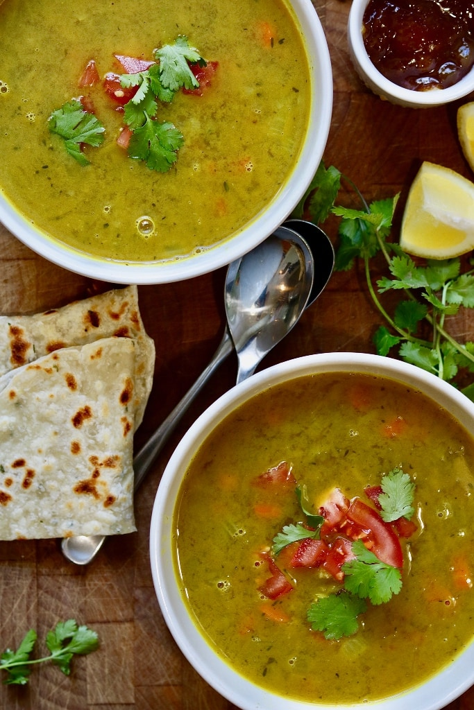 two bowls of mulligatawny soup on a wooden table