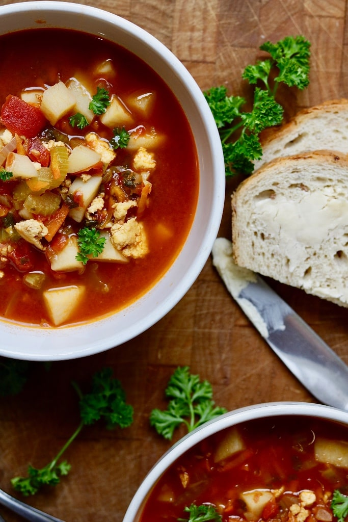 vegan hamburger soup in a white bowl with two pieces of buttered bread