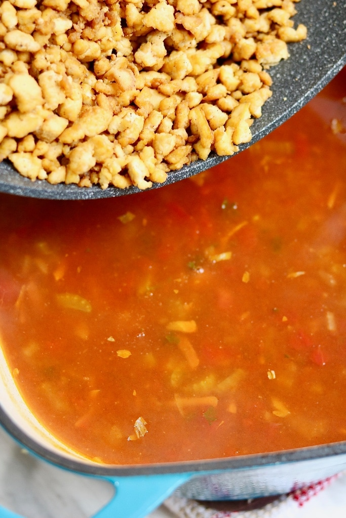 vegan hamburger soup in a pot with tofu crumbles being added