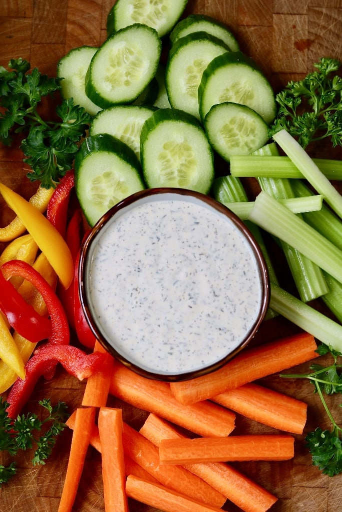 vegan ranch dressing on a wooden cutting board surrounded by sliced vegetables