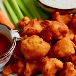 cauliflower buffalo wings on a platter with celery carrots and two dips