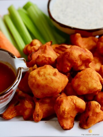 buffalo cauliflower wings on a platter with celery carrots and vegan ranch dressing