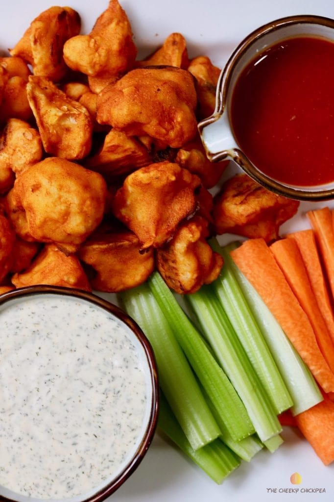 cauliflower buffalo wings on a platter with carrots celery and two dips