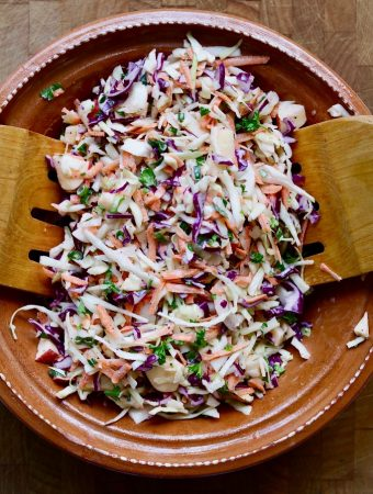 classic vegan coleslaw in a brown bowl with wooden tongs