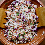 vegan coleslaw in a salad bowl tossed with creamy dressing
